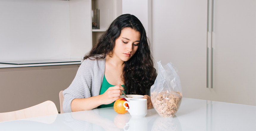 Sad young woman having breakfast in a modern kitchen